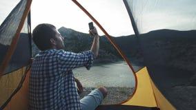 En ung man ligger i ett campa tält g?r ett foto p? en smartphone Fotografier ett härligt landskap lager videofilmer