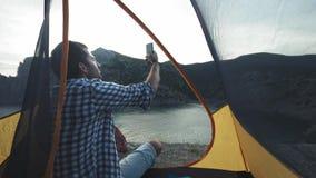 En ung man ligger i ett campa tält g?r ett foto p? en smartphone Fotografier ett härligt landskap stock video