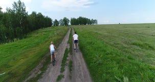 En ung man med en barnridning cyklar på en landsväg Skjuta från ett surr Sportar utomhus Royaltyfri Bild