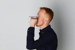 En ung man med en råna av te eller kaffe Han behog Vit bakgrund Rödhårig manmannen med vit rånar Royaltyfria Foton