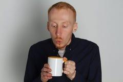En ung man med en råna av te eller kaffe Han behog Vit bakgrund Rödhårig manmannen med vit rånar Royaltyfri Fotografi