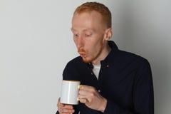 En ung man med en råna av te eller kaffe Han behog Vit bakgrund Rödhårig manmannen med vit rånar Fotografering för Bildbyråer