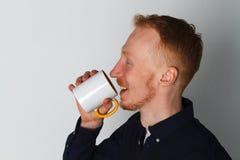 En ung man med en råna av te eller kaffe Han behog Vit bakgrund Rödhårig manmannen med vit rånar Arkivfoton