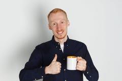 En ung man med en råna av te eller kaffe Han behog Vit bakgrund Rödhårig manmannen med vit rånar Royaltyfria Bilder