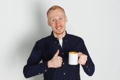 En ung man med en råna av te eller kaffe Han behog Vit bakgrund Rödhårig manmannen med vit rånar Arkivbild