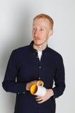 En ung man med en råna av te eller kaffe Han behog Vit bakgrund Rödhårig manmannen med vit rånar Royaltyfri Foto
