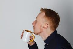 En ung man med en råna av te eller kaffe Han behog Vit bakgrund Rödhårig manmannen med vit rånar Arkivbilder