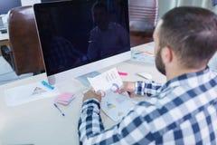 En ung man med ett skägg arbetar med ett schema arkivfoton