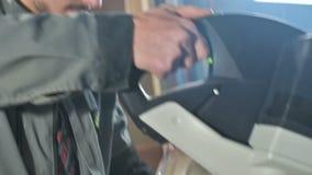 En ung man med ett skägg i gråa overaller vid yrke som en snickare arbetar med en rund bitande maskin i hans hem lager videofilmer