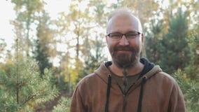 En ung man med ett skägg och exponeringsglas ler och jublar på kameran på bakgrunden av skogen, hans framsidafinnar arkivfilmer