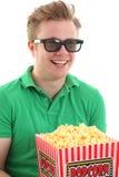 En ung man med exponeringsglas 3D och ett popcorn ösregnar Arkivfoto