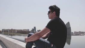 En ung man med exponeringsglas sitter vid pölen i ottan på en varm sommar stock video