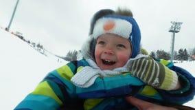 En ung man med en gladlynt pojke med en berg-och dalbanaritt i vintern på isen Stilig farsa och son som skrattar i a stock video