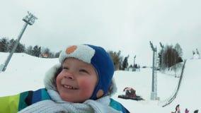 En ung man med en gladlynt pojke med en berg-och dalbanaritt i vintern på isen Stilig farsa och son som skrattar i a arkivfilmer