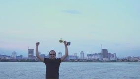 En ung man med en kopp i hans händer jublar i sportseger Danser och hopp på aftonstad Begrepp som seger stock video