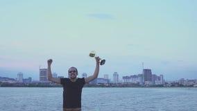 En ung man med en kopp i hans händer jublar i sportseger Danser och hopp på aftonstad Begrepp som seger lager videofilmer