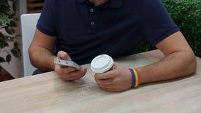 En ung man med en regnbågesymbolism i ett kafé, bruk en telefon Royaltyfri Bild
