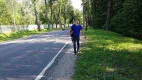 En ung man med en ryggsäck fångar en ritt på sidan av vägen lifta Ekonomiskt lopp lager videofilmer