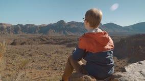 En ung man med en smartphone gör ett foto video skytte på kanten av ett vulkaniskt lavaavbrott lager videofilmer