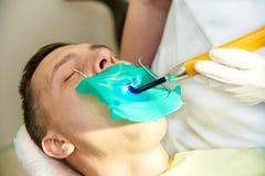 En ung man med stängda ögon i den tand- stolen Tandläkaren arbetar med en tand- polymerisationslampa arkivbilder