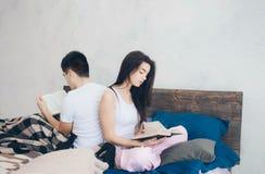 En ung man och en kvinna sitter på sängen och läsningen en bok Romantisk morgon hemma Royaltyfri Fotografi