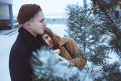 En ung man och en flicka som går på det snöfältet och skrattet arkivfoto