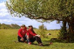 En ung man och hans flicka med longboards vilar nära ett träd Royaltyfria Foton
