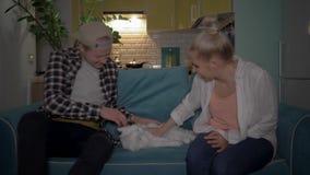 En ung man och hans flickvän sitter ner till en ensam katt på soffan Begrepp: ta omsorg av husdjuren 4K lager videofilmer