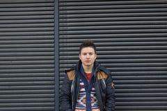 En ung man på en svart bakgrund Arkivfoto