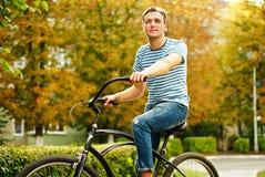En ung man på en cykel ser in i avståndet Royaltyfri Bild