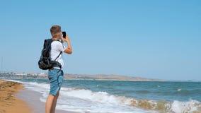 En ung man promenerar den sandiga stranden och skjuter en seagull på en mobiltelefon arkivfilmer
