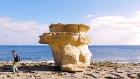 En ung man promenerar en stenig kust förbi en enorm kullersten Blått vatten, turist, går, vilar, seglar utmed kusten lager videofilmer