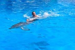 En ung man rider delfin, pojkesimning med delfin i bl?tt vatten i vattenp?len, havet, havet, delfin sparar en man royaltyfri foto