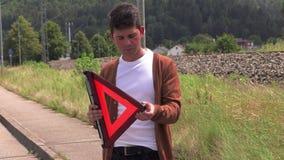 En ung man sätter ett nöd- tecken stock video