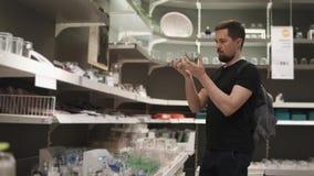 En ung man söker efter glasföremål för hans stilfulla lägenhet lager videofilmer