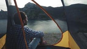 En ung man sitter i ett campa tält Tycker om en härlig sikt av havet och bergen Fotvandra affärsföretag i Krimet stock video