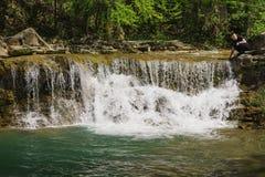 En ung man sitter nära en liten vattenfall och en klar bergflod Zhane nära byn Vozrozhdenie royaltyfri fotografi