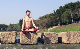 En ung man sitter på en sten i den Lotus positionen på bakgrunden av floden i parkera Arkivfoto