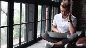En ung man sitter på en fönsterbräda och arbetar genom att använda en bärbar dator och en smartphone lager videofilmer