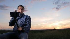 En ung man sitter på solnedgången och gör selfie på en mobiltelefon Härlig himmel bakom arkivfilmer