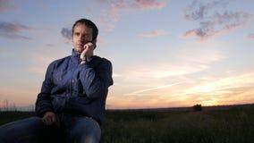 En ung man sitter på solnedgången och talar på hans mobiltelefon Härlig himmel bakom stock video