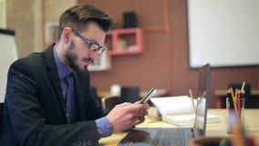 En ung man som använder telefonen på hans arbetsplats stock video
