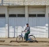 En ung man som cyklar p? gatan arkivfoto