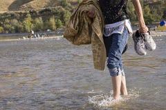 En ung man som går i grunt vatten vid kalt, Foots Arkivbild