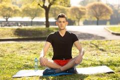 En ung man som g?r yoga i gr?splanen, parkerar begrepp av en sund livsstil arkivbilder
