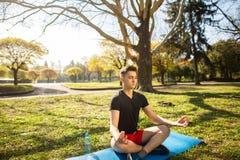 En ung man som g?r yoga i gr?splanen, parkerar begrepp av en sund livsstil royaltyfria bilder