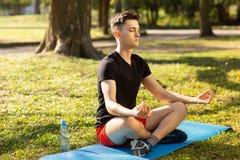 En ung man som g?r yoga i gr?splanen, parkerar begrepp av en sund livsstil royaltyfri bild