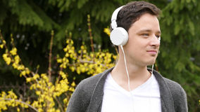 En ung man som lyssnar till musik vid vit hörlurar parkerar in - botaniska trädgården under älskvärd vårtid Royaltyfri Fotografi