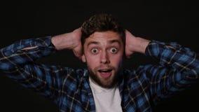 En ung man som mimicing mot en svart bakgrund arkivfilmer