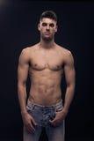 En ung man som poserar, shirtless abs för jeans, förkroppsligar Arkivfoto